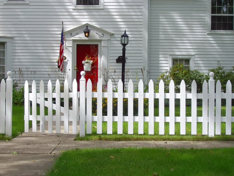 Simple white picket fence in front of a gray house.