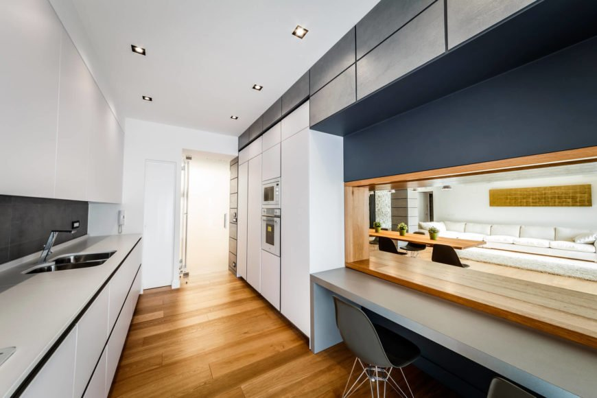 """The kitchen is awash in high contrast, with bright white cabinetry meeting the dark hued """"monolith"""" wall and warm natural wood tones. The living room can be seen through the void at right."""