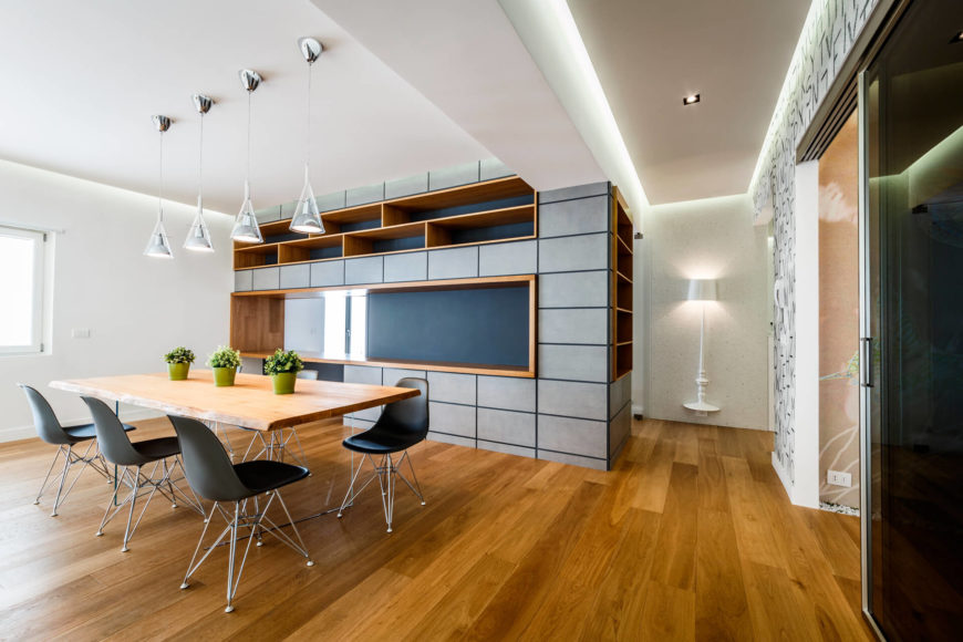 Rounding the corner in the hall, one has access to the kitchen at left and bedroom and bathrooms to the right. Abundant wood shelving is built into the large dividing wall.