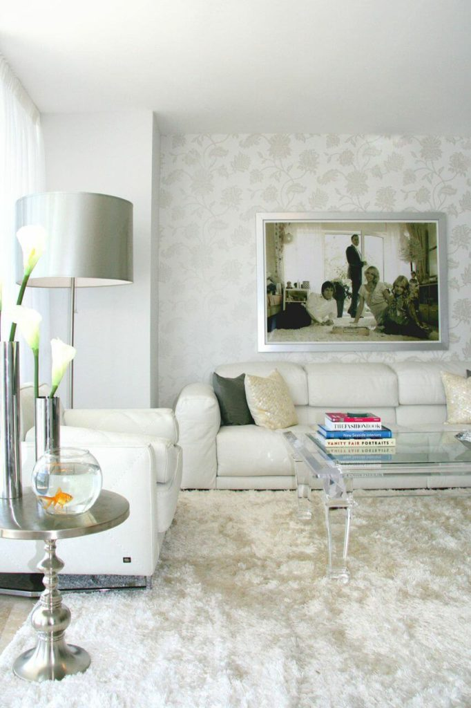 A close up of the living room area, showing the nearly transparent coffee table, chrome side tables, and the subtle floral wallpaper behind the sofa. A unique family photo hanging above the sofa further personalizes the space.