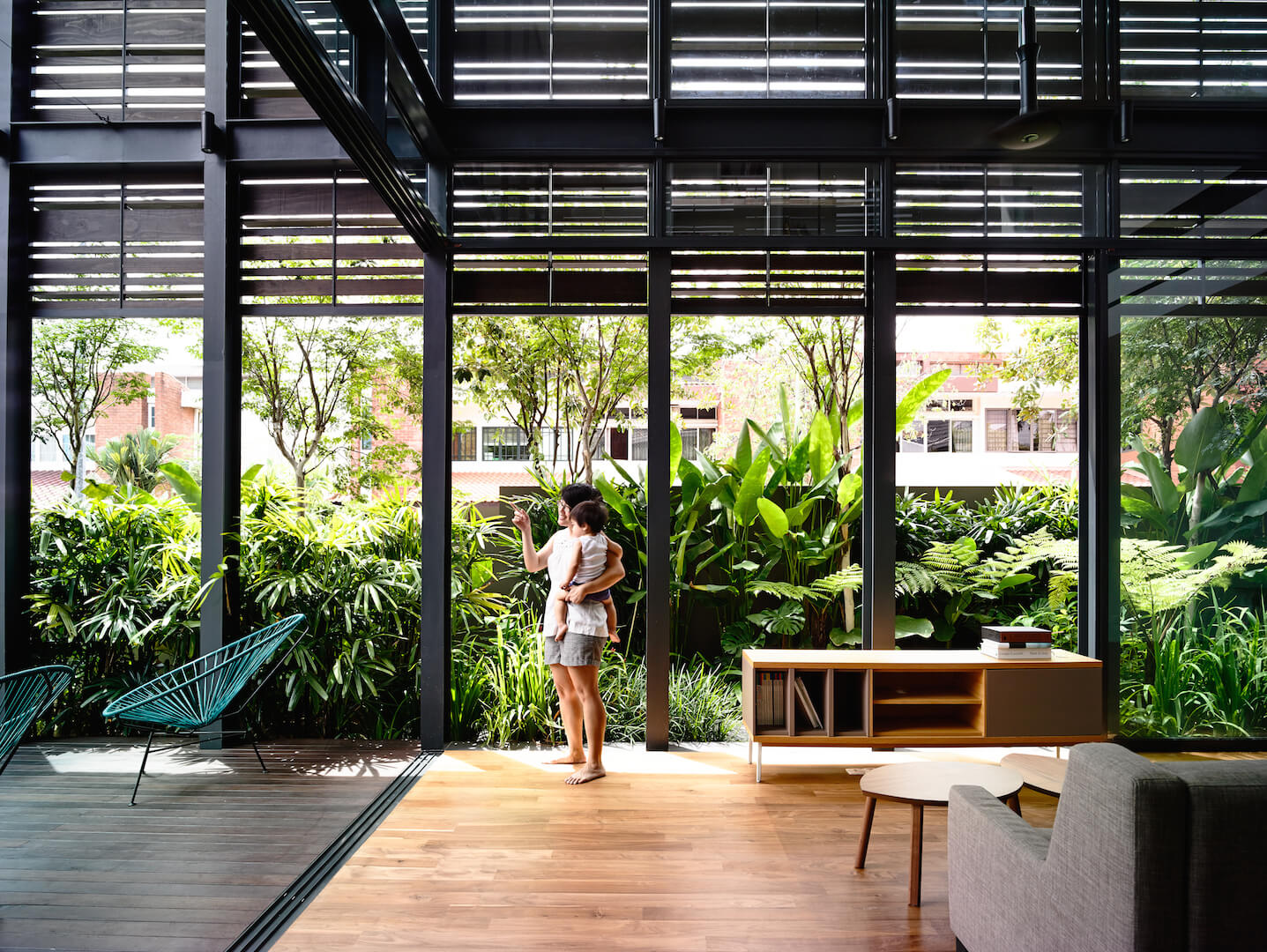 This shot of the living room and sunroom from the entrance to the space shows the landscaping just outside with massive, lush foliage that nearly blocks out the apartment complex across the street.