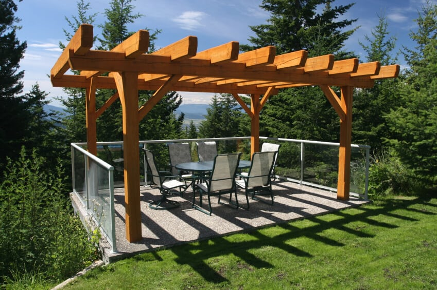 This simple but elegant stone mosaic patio is covered by a warm-toned natural wood pergola. Since this dining area is perched on the edge of a small cliff, glass balustrades enclose the area on three sides. A pergola is a wonderful way to cover an existing patio at a lesser cost than extending a section of roof.