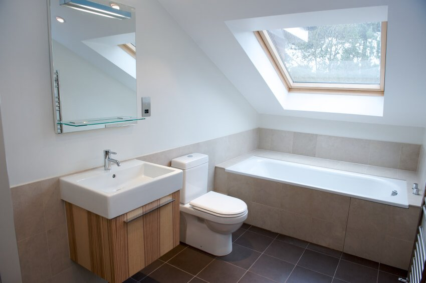 This minimalist bathroom features clean lines, modern design, and a large skylight to lend daily sunshine to this smaller area.