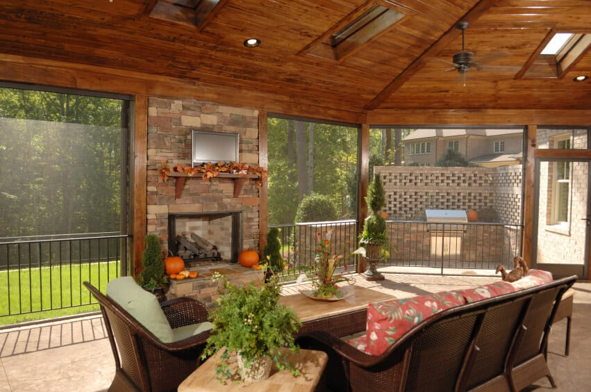 This screened in patio has an enormous arched wooden ceiling with ample skylights. A screen door lead outside to another small patio area with a grill. A stone privacy wall helps shield this entertaining area from the neighbors.