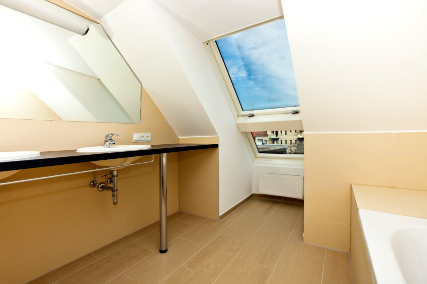 The above skylight offers a gorgeous blue sky with cottony clouds, while the rest of the bathroom delights in angles, minimalist design, and the buttery richness of its walls.