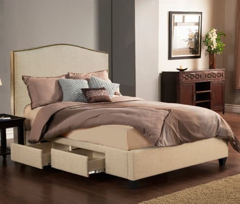 An upholstered bed with a regal silhouette and a golden nail head trim. The bed includes four drawers below and is in a polyester blend fabric.