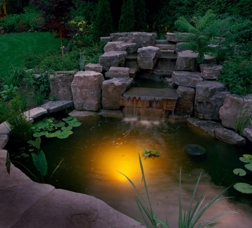 At nighttime, this pond with a small waterfall lights up from below, casting a haunting glow upon the surface of the pond.