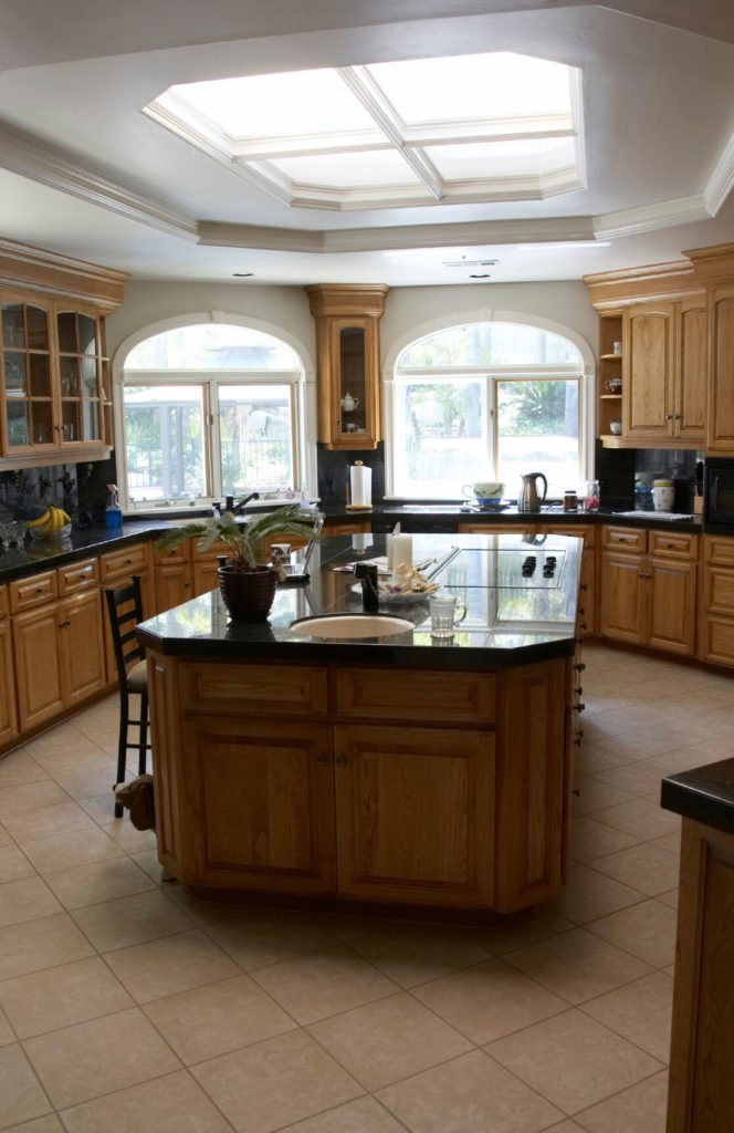 This kitchen has an interesting skylight. The skylight is shaped almost like a window, with traditional frames and a unique shape.