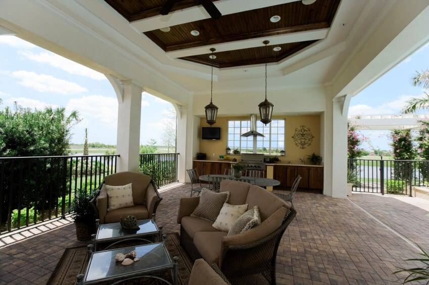 While many of the covered patios in this collection are connected directly to the main home, this enormous patio's covered eating and relaxation section requires a short walk through the sunny portion of the stone patio. Elegant wicker furniture and a full outdoor kitchen make this space both functional and utterly relaxing.