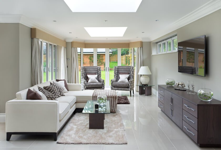 This contemporary living room brings together neutral colors and elegant gray floors under two square skylights. The natural light giving the modernized living room a peaceful atmosphere.