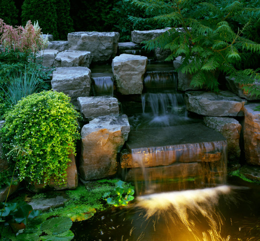 A closer look at the waterfall section of the above water feature, showing the carefully placed stone blocks and the landscaping that makes the man-made structure feel far more natural.