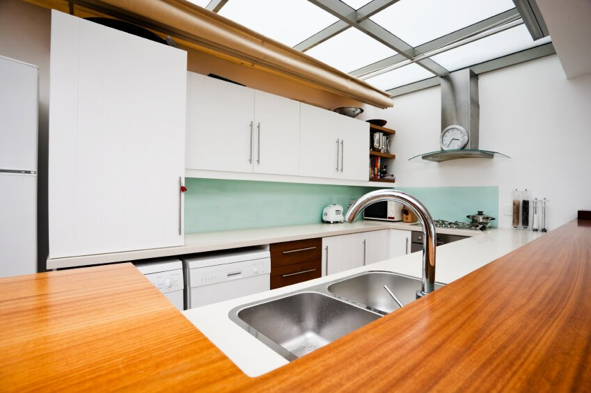 This old-school kitchen has a splash of aqua on the walls, and a beautiful amber hardwood. Large skylights line the ceiling as the main source of light in this quaint space.