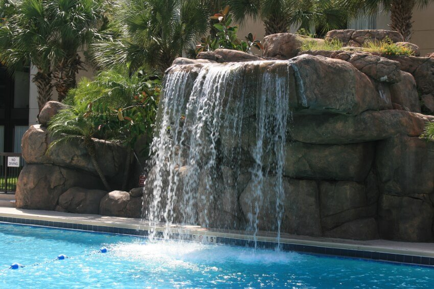 A large artificial waterfall on the side of a resort pool. Palms grow up between the artificial stones.