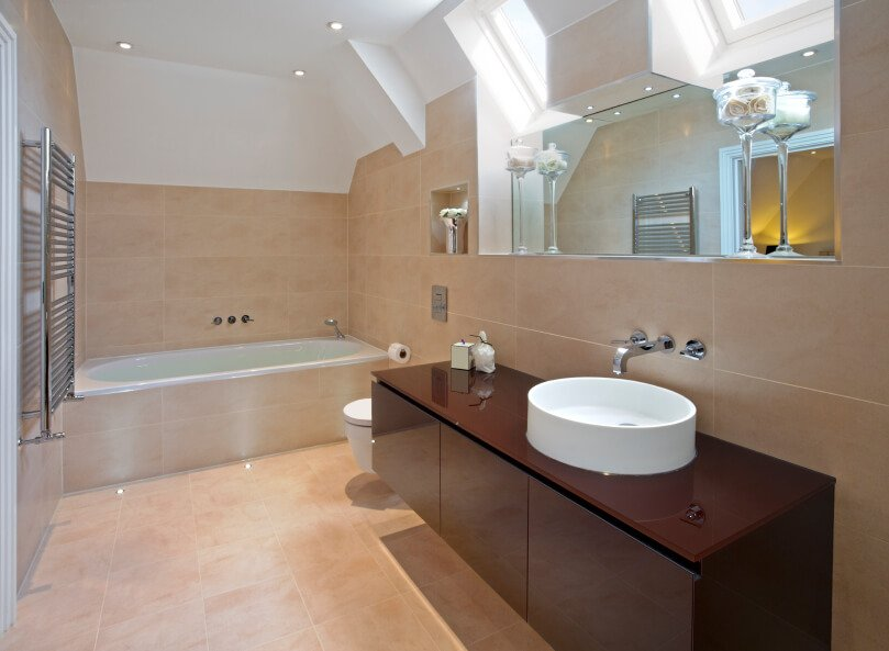 Skylights find their home above a large mirror overlooking a striking modern vanity with unusual basin. The rich, dark wood of the vanity offers interest in contrast to the rest of the creamy peach tiled space.