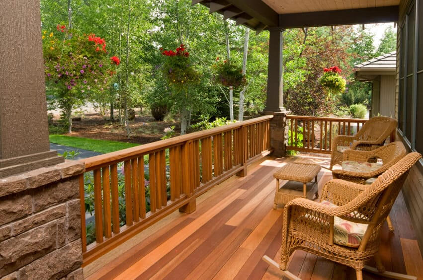 The multi-tonal wood decking of this shallow covered porch creates an elegant and rustic atmosphere that is echoed by the light wicker rocking chairs. Gloriously full hanging baskets add a floral, organic element to this space.