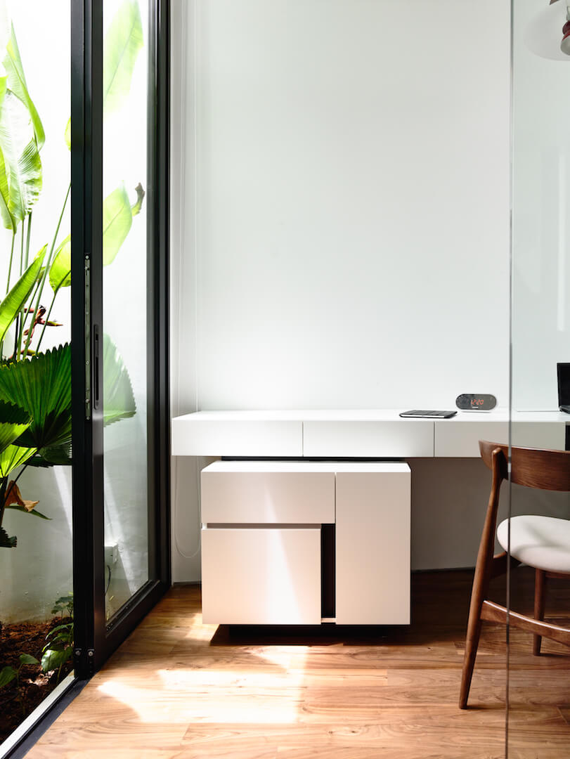A close up on the minimalist white desk with multiple pull-out drawers. The glass-paneled door to the terrace can be opened to let a cool or warm breeze in while working.