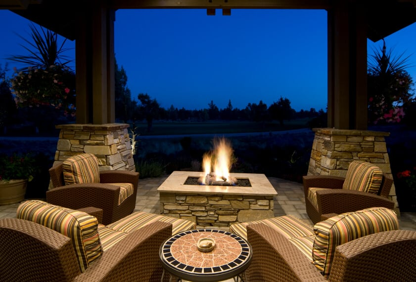 Wooden columns with stone bases support the soaring ceiling of this covered patio. A matching stone fire pit at the center denotes this space as one for nighttime entertainment.