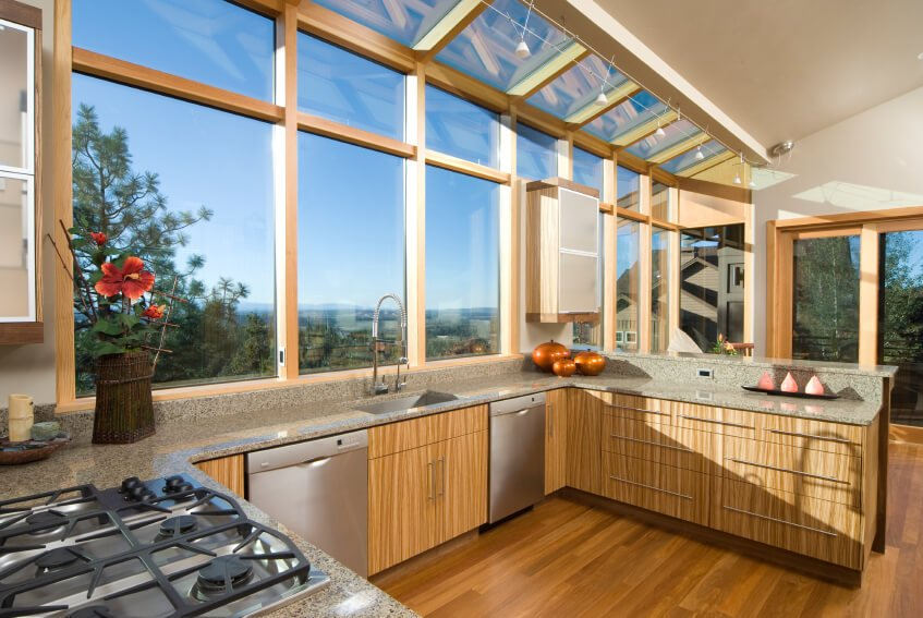 This illuminated kitchen has lots of windows and skylights for a full view and natural light. The textured wood on the cabinets and floor really give it a wild look.