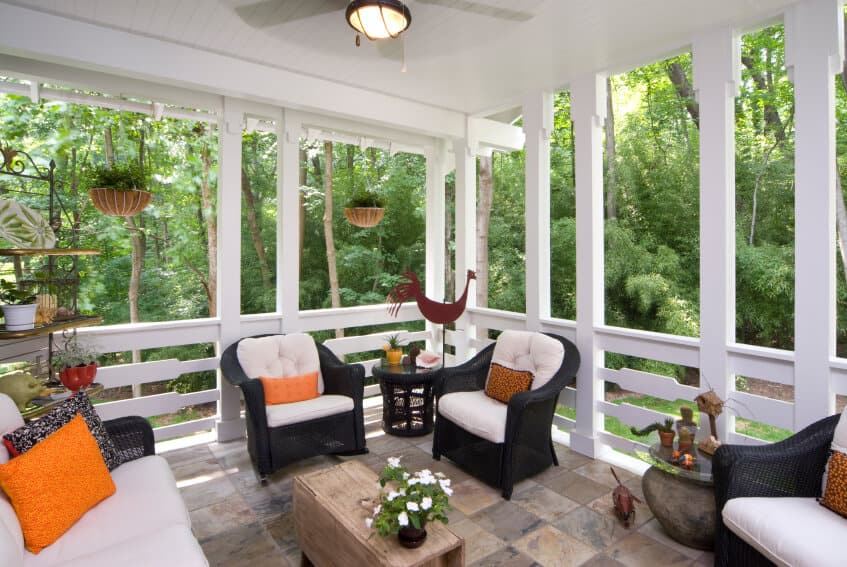 This lovely white covered stone patio has country-chic railings in between each support beam. Small green hanging baskets on the left add another element of organic to this eclectic space. The rustic coffee table has two leaves that can be extended to create a larger coffee table as needed.