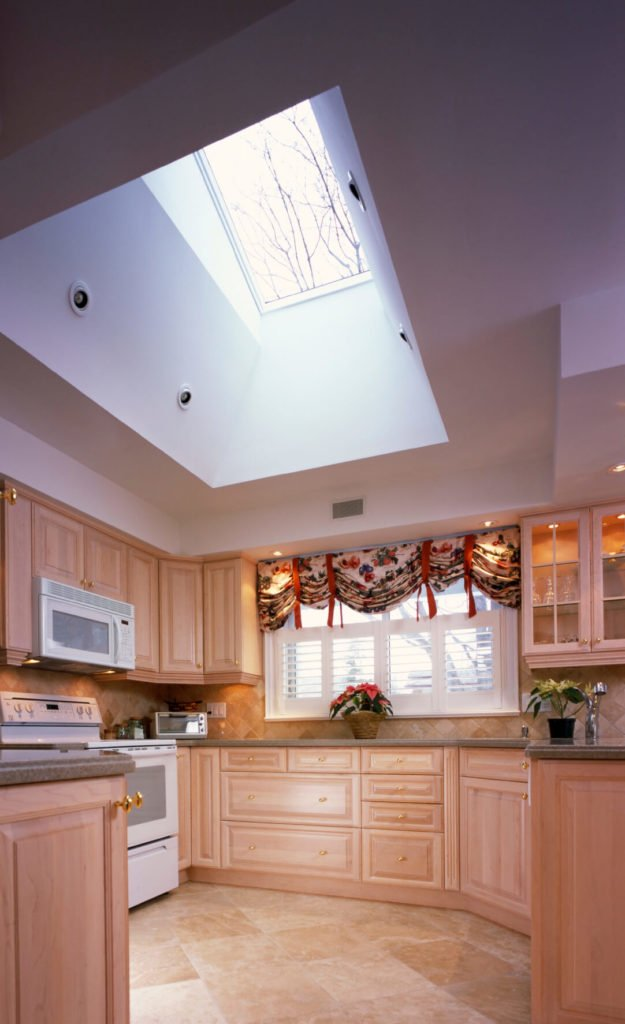 This lovely natural light hardwood kitchen is is full of storage space and subtle designs. A skylight is angled to hit a wall before filtering down into the kitchen, to give a soft light, rather than a harsh one.