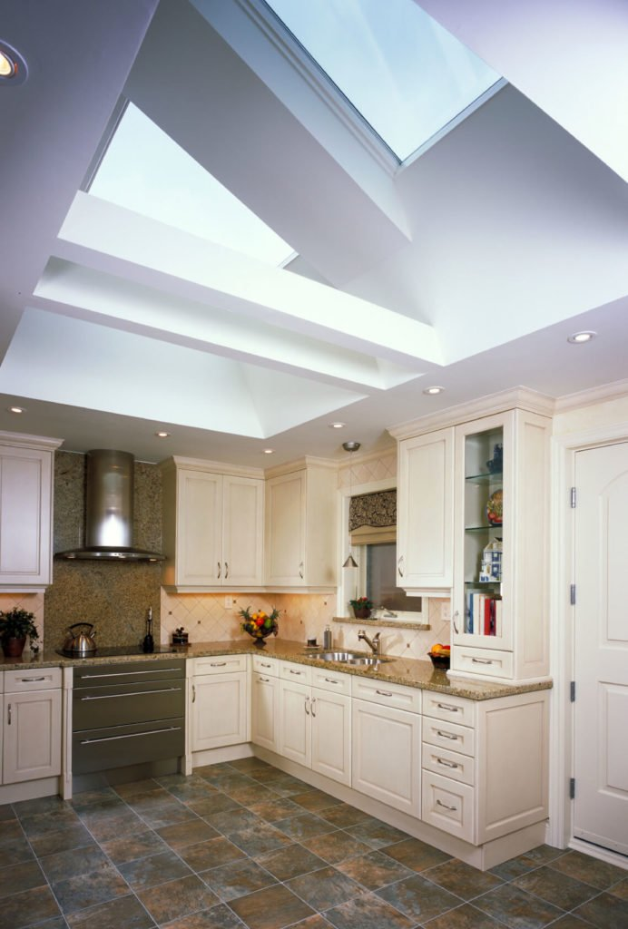 Multi-toned tile and a rich granite countertop gives this space a really traditional look. This kitchen also has a lot of unique angles in the ceiling, and skylights accentuating the interesting bends.