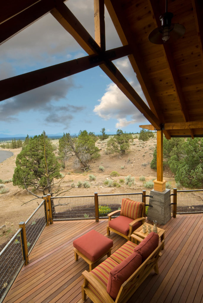 A dune overlook patio in wood with steel railings. The sharply arched roof allows air to circulate above the wooden patio furniture while still protecting the occupants from sudden sprinkles and the hot midday sun.