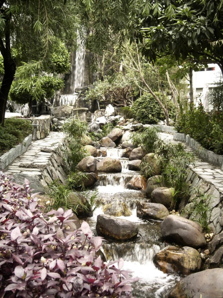 Two narrow stone paths run on either side of this multi-tiered waterfall river. In the background is a much larger waterfall tucked between trees and other landscaping.