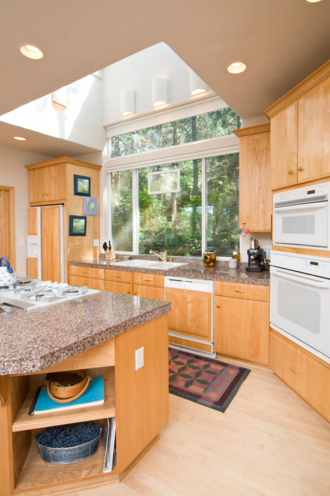 Beautiful light hardwood (even on the dishwasher!) and sleek granite countertops in this kitchen make a striking combination. A skylight tunnels from the ceiling up to the roof, giving the room plenty of light without overbearing the space.