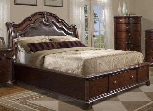 A rich cherry sleigh bed frame with storage in the footboard. The luxurious padded headboard has carved molding with a brass nail head trim.