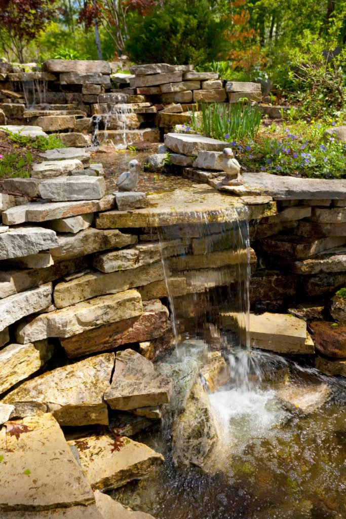Layered sedimentary stones make up this water well and waterfall complex surrounded by small wildflowers and grasses. Two stone statuettes of ducks sit on either side of the main falls.