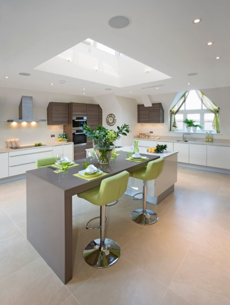 This kitchen has beautiful earthy tones of green and brown. A large skylight adds to the natural feeling, with sunlight dripping onto the subtle hues.