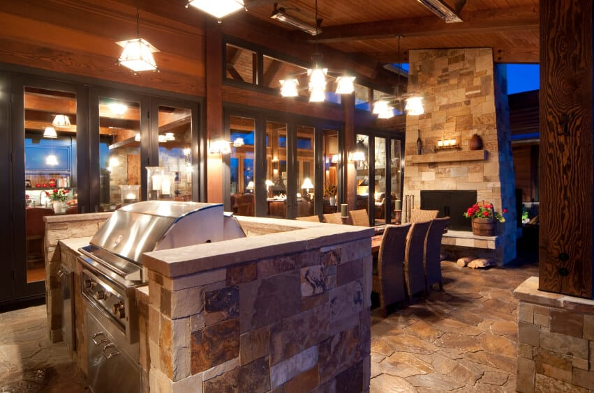 As a more modestly sized stone patio, layout is incredibly important. The combination of kitchen and outdoor dining room with an enormous screened wood-burning fireplace at the far end makes excellent use of the limited space and allows the functions to flow together. Large matching lights keep this space well lit into the night.