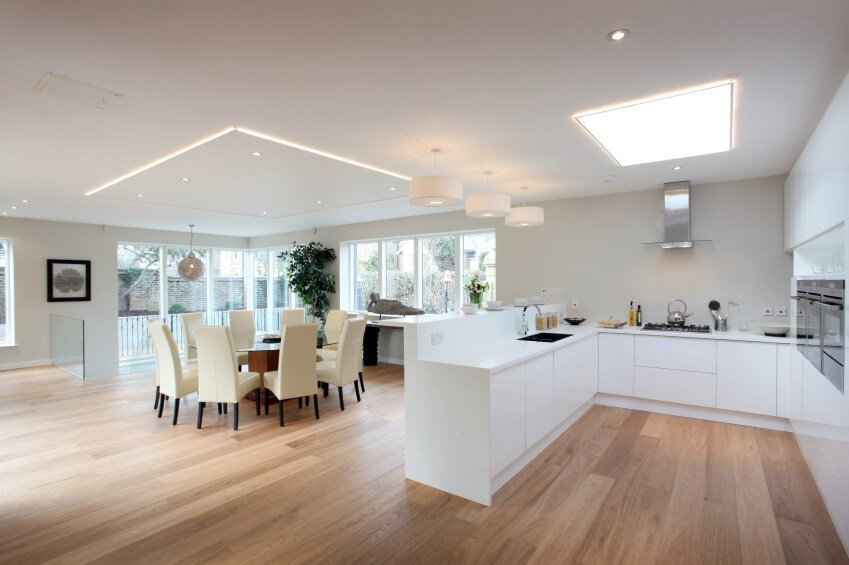 This all white kitchen is incredibly modern and graceful. A skylight sits over the kitchen as the main source of lighting in this chic room.