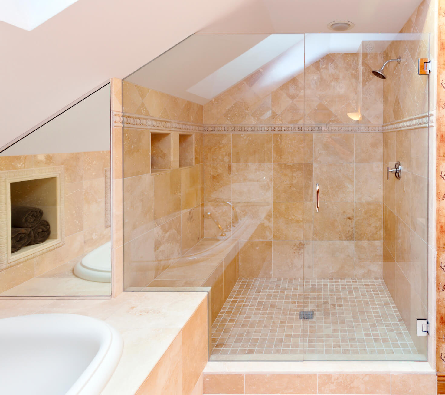 A peek of the corner of a skylight can be seen in this heavily tiled bathroom space.