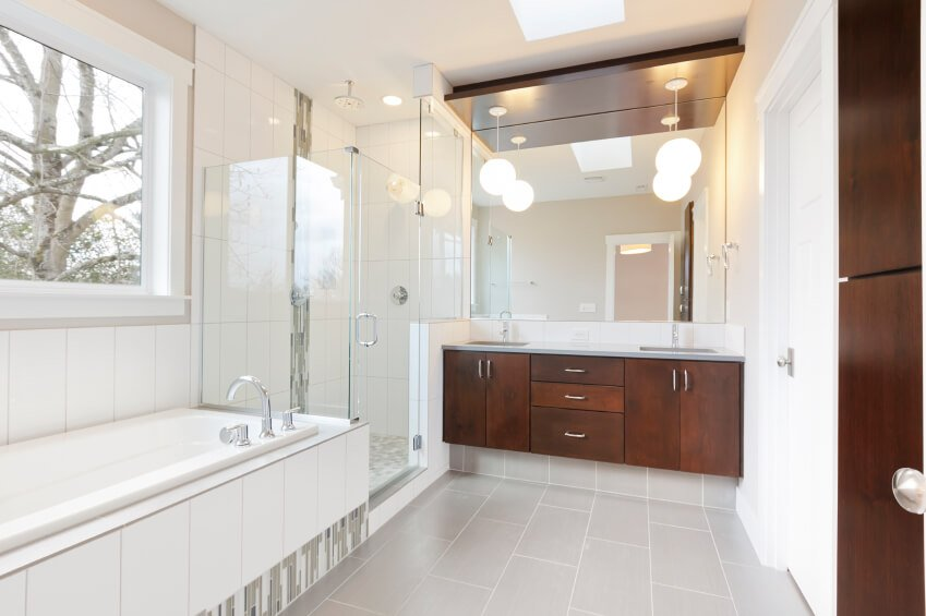 This light bathroom space offers contrast in the rich wood of the double vanity and cabinetry.