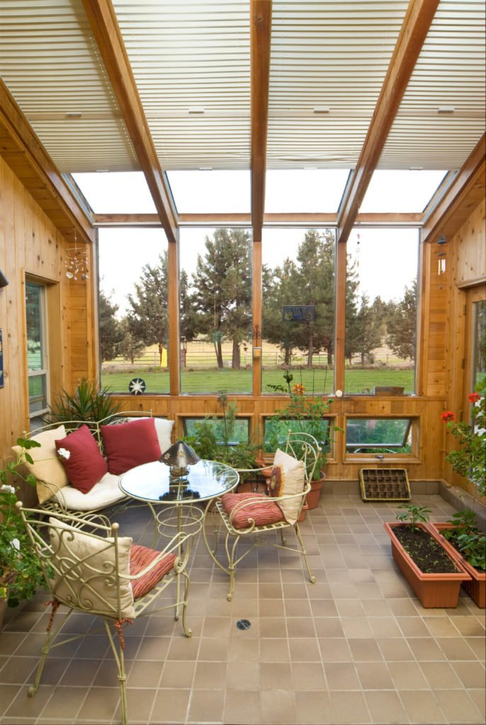 This beautiful three-season room is encased in light pine and feature a number of windows that extend from the roof down the side. Smaller windows can be vented to let cool air flow into this greenhouse-like room. Motorized shades can block some of the sun, if needed.
