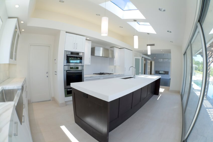 Rich dark hardwood contrasts the polished whites and marble of this kitchen. The skylights dapple the room with a natural and enchanting shimmer.