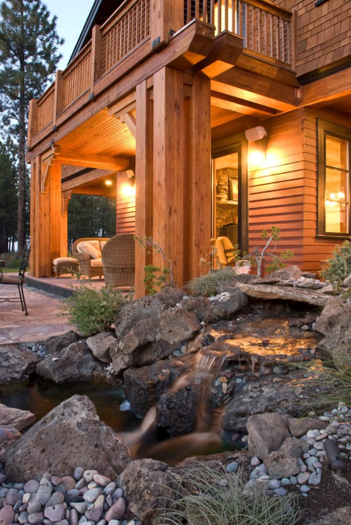 A beautifully rustic covered porch area with an extended uncovered patio. This view is from just on the other side of the artificial garden waterfall. The close proximity of the waterfall to the wicker seating area ensures that guests will hear the soothing sound of water moving over the rocks.