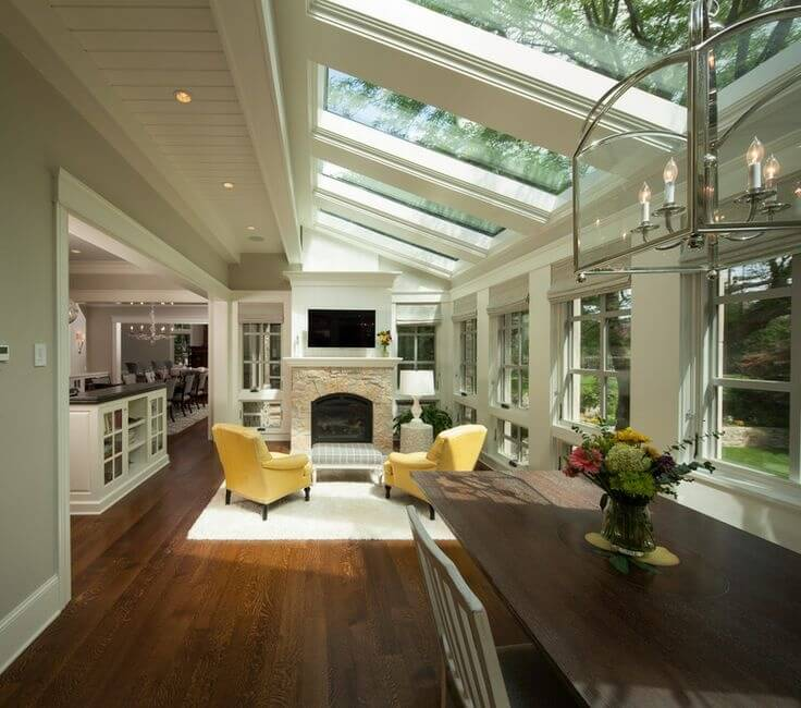 This wild living room has a great woodland feeling with the line of skylights angled down into the living room. The soft yellow of the arm chairs contrasts the contemporary colors of the rest of the space.