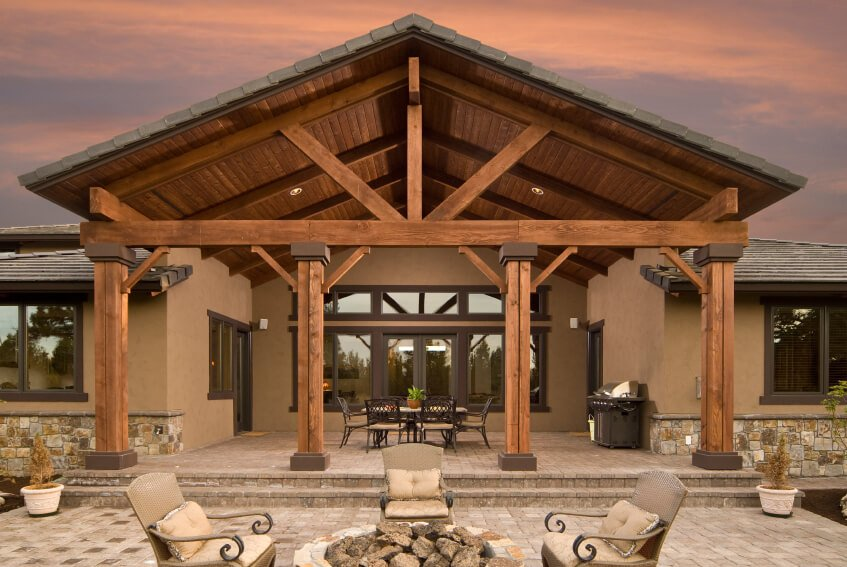 Even the rear of this home includes a grand architectural statement. Tall wooden beams lead up to a massive arched patio cover. The beautiful stone patio continues into a fire pit area with four elegant armchairs.