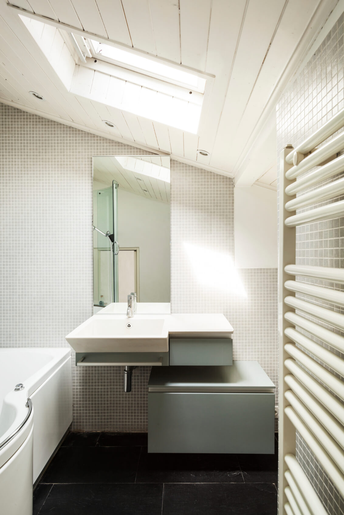 A close up of the sink area reveals a matte gray storage cabinet and additional detail of the skylight.