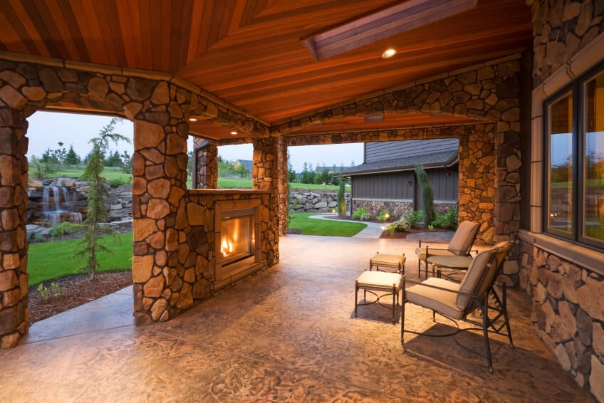 The cedar ceiling of this stone-encased patio provides a stunning, rich tone to the more neutral stone walls and floor. An enclosed fireplace is contained within one of the walls, and a small opening provides a view out to the backyard, which includes a large stone waterfall.