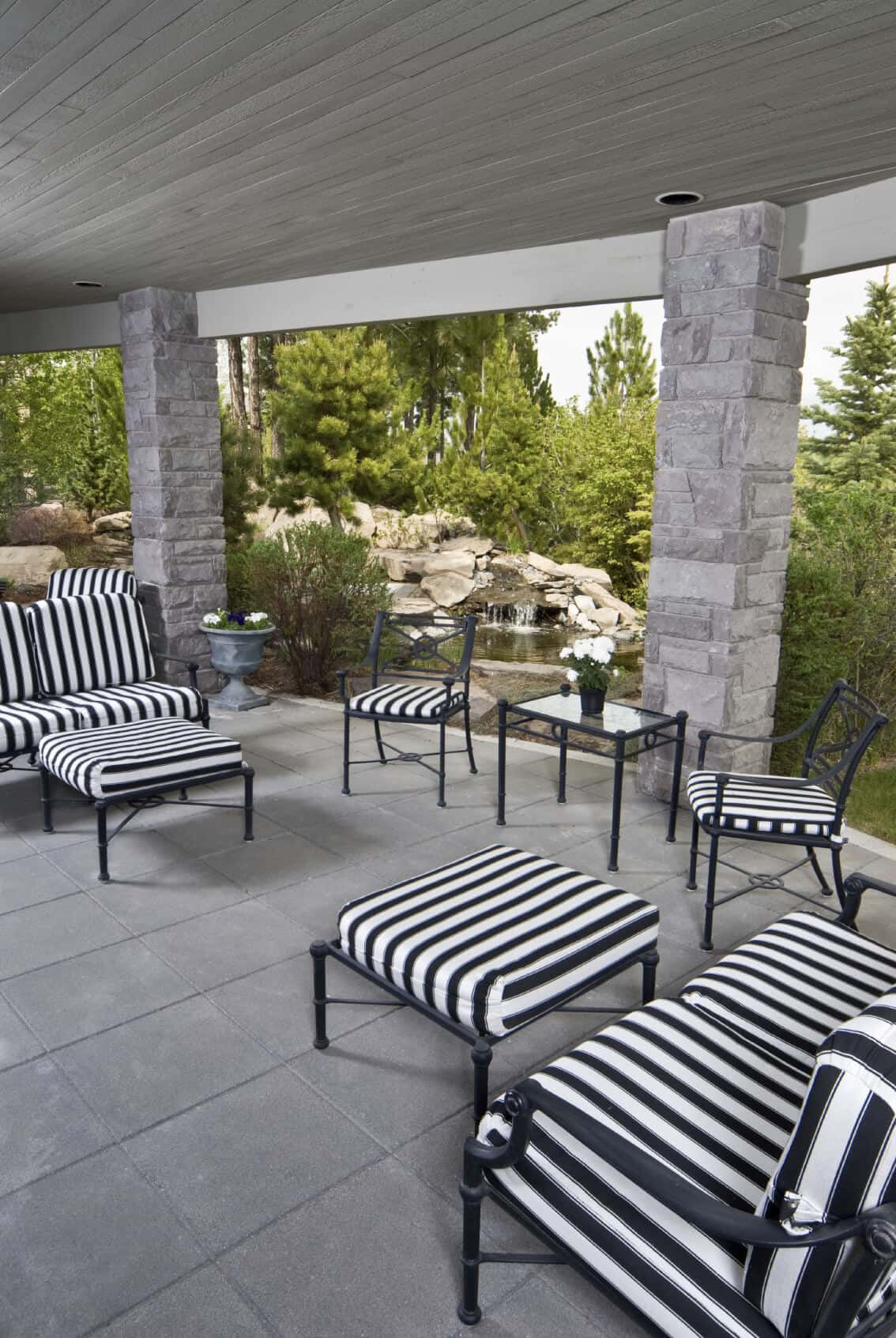 Mesmerizing black and white striped patio furniture provides a striking contrast to the light gray stone tile and columns of this covered patio. In the background is a small waterfall and pond.