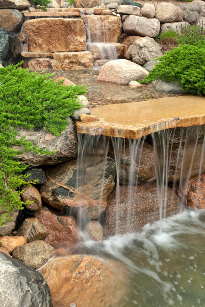 A closer look at the side of the waterfall's shelf. A low evergreen ground cover is creeping across the rocks towards the water.