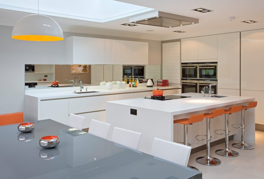 This whimsical kitchen is nearly all white with fun splashes of orange dappled throughout. The natural light from the skylight brings out the warm colors in this room.