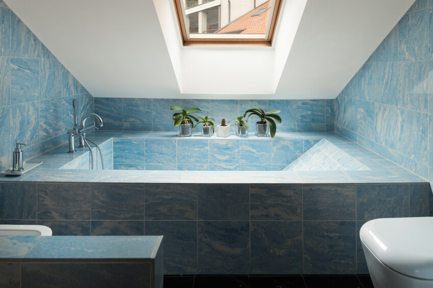 This swirling blue tiling of this impressive bathtub brings to mind a cloudy sky or crashing waves, with either interpretation leading to optimal relaxation. The small wood framed skylight shines just the right amount of light on the space, while decorative plants offer a pop of color as they soak up the sunshine.