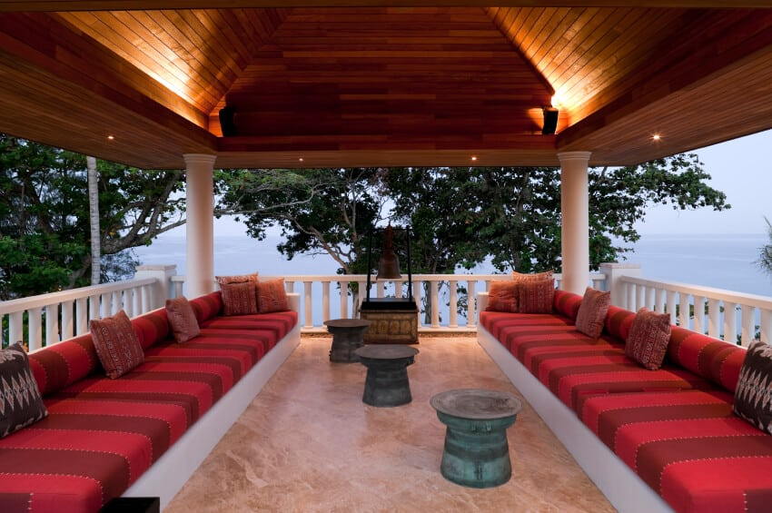 This covered terrace features luxurious warm-toned marble flooring and richly striped bench seats running along two sides. The elevation of this terrace allows for a glorious view of the water.
