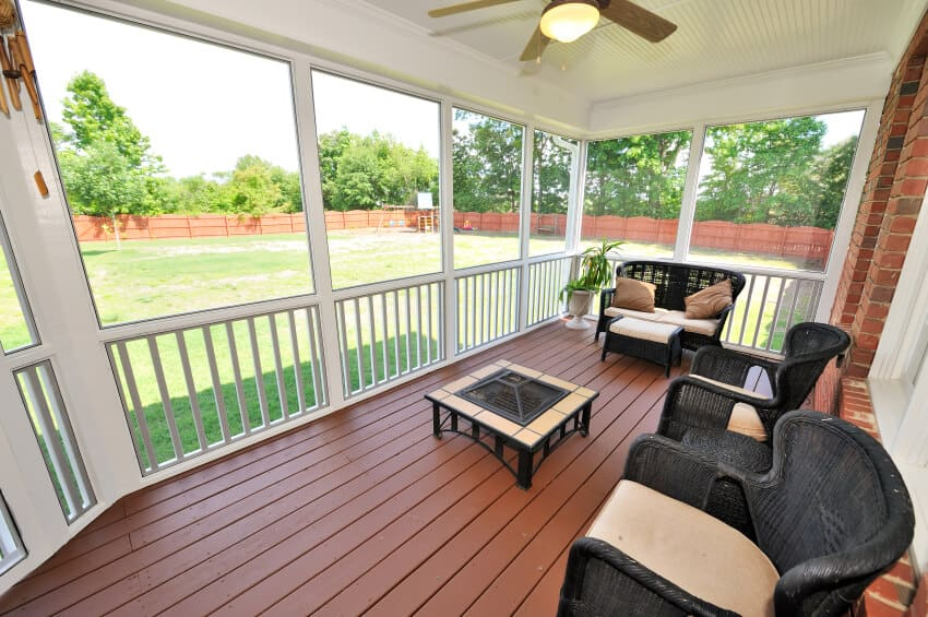 This simple sundeck has a set of black wicker chairs and windows that peer out into the massive, open backyard.