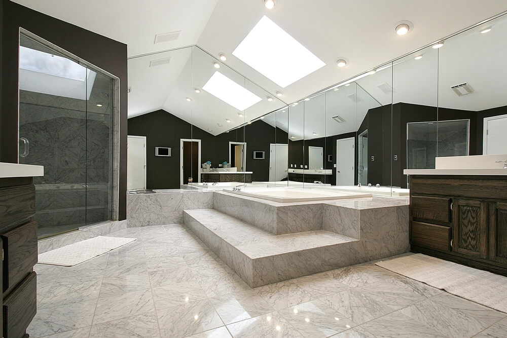 This stunning bathroom features glossy squares of stone tile, soaring ceilings, and wall length mirrors contributing to the extraordinary illusion of increased space. A skylight hangs above, reflecting off mirrors and allowing light to bounce around the room. Dark walls and cabinetry offer stark contrast to the muted tones of the rest of this impressive space.
