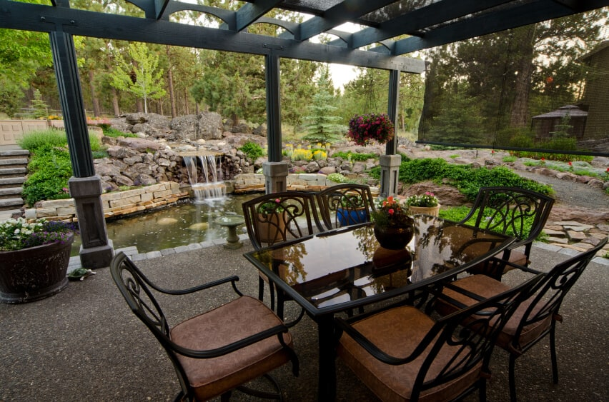 An elegant black pergola with mesh between the planks covers this pebble patio. Stone walkways lead around and behind the waterfall and pond.